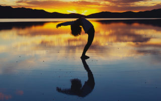 Woman doing a back bend with sunset behind her
