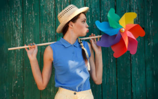 woman blowing on a pinwheel