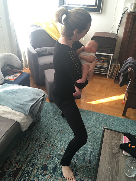 Doing a goddess pose yoga pose while holding a baby