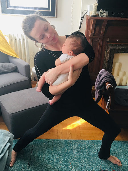 Reverse Warrior pose while holding a baby